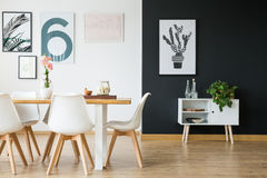 Dining room with plants. Black and white wall in dining room with plants royalty free stock image