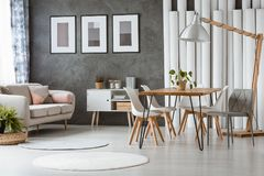 Dining room with plastic chairs. Bright dining room with white plastic chairs and relax space with beige couch and pink cushions Stock Photo