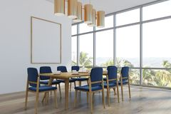 Dining room with a poster, palms, corner. Dining room interior with loft windows, white walls and a wooden floor. A long table with blue chairs and a poster on Royalty Free Stock Images