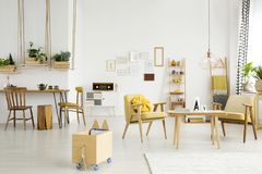 Dining room with relax area. Spacious dining room interior with wooden crates on swings and yellow armchairs in the relax area Stock Images