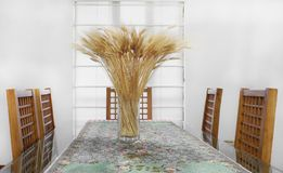 Dining room table. Dining room glass table decorated with wheat on a vase Royalty Free Stock Photos