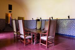 Dining room table and chairs. Old dining room with tiled walls and floor with an antique table and high back chairs stock photos