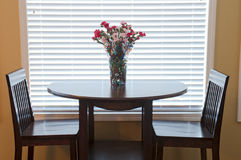 Dining Room Table and Chairs. Decorated with flowers in backlit interior Stock Photography