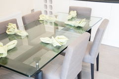 Dining room with table and chairs. Interior of modern dining room with glass top table and cloth chairs Stock Photography