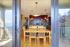 Dining room table through open balcony doors. Royalty Free Stock Photography