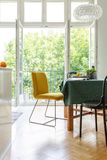 Dining room table with yellow and black chairs , real photo. Vertical view of dining room table with yellow and black chairs and green tablecloth, stylish stock photography
