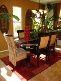 Dining Room Tropical. Beautiful tropical dining room, bold colors of red and gold and green dark wood and wicker chairs red rug over tile floors Royalty Free Stock Photos