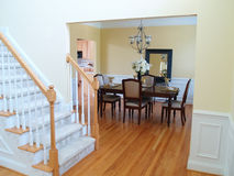 Dining Room View. A well staged dining room viewed from the foyer with the staircase in the foreground Stock Photo