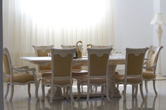 Dining room with white wooden furniture. Dining room with white wooden furniture filled with sunlight Stock Images