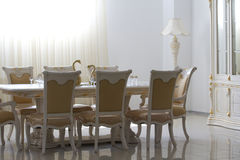 Dining room with white wooden furniture. Dining room with white wooden furniture filled with sunlight Royalty Free Stock Image