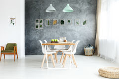 Dining room with window. Pillows in wicker basket in the corner of dining room with window Royalty Free Stock Images