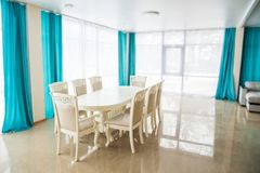 Dining room with wooden table and chairs. Bright interior. Blurred Background Royalty Free Stock Photo