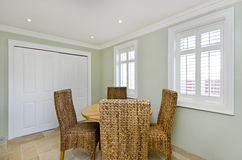 Dining room with wooden table and rattan chairs Stock Photography