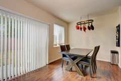 Dining room with wooden table set and exit to the back yard. Stock Photos