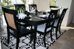 Dining set in black and white. An upscale formal dining room is done in trendy black and white. Dining table is on a white and black area rug which is on a tile stock images