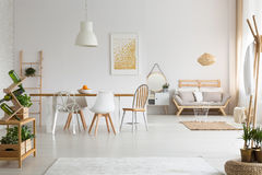 Dining space and living room in apartment. Modern dining space and simple living room in elegant lagom apartment Stock Photos