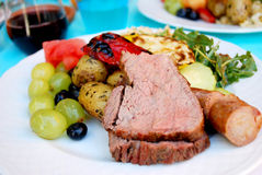 Dining in the Summer. Picture focused on the center of tri-tip with colorful food around Royalty Free Stock Photography