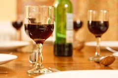 Dining table. With a wine bottle and glasses filled with red wine Stock Photo