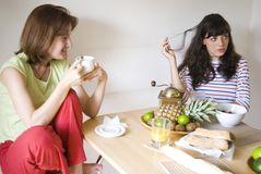 At the dining table. Two young women sit at the dining table, enjoying the fruit, bread, coffee and juice Royalty Free Stock Images