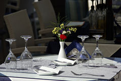 Dining Table. At restaurant, vase with fresh flowers, shiny clean glases Royalty Free Stock Photo