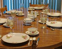 Dining Table. Set up with plates, glasses and silverware Stock Photo