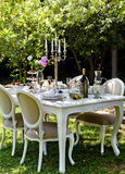 Dining table in backyard. White romantic dining table with candelabra in backyard Stock Photo