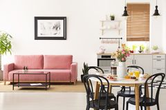 Dining table with breakfast and fresh flowers standing in bright. Apartment interior with pink sofa, black and white poster and kitchenette with pastel stock photos