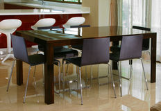 Dining table and chairs. Dark wood dining table with glass top Royalty Free Stock Image