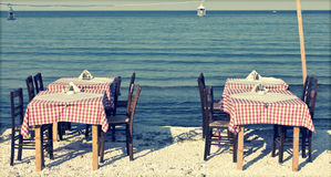 Dining table and chairs on the beach - retro styled photo Stock Photography