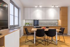 Modern and open kitchen with window. Dining table and chairs in modern, bright and open kitchen with window royalty free stock photos