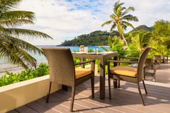 Dining table with chairs on wooden decking, by the sea, Mahe island, Seychelles Stock Photos
