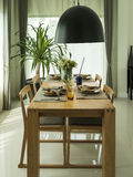 Dining table and comfortable chairs in modern home Stock Photos