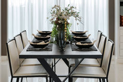 Dining table and comfortable chairs in modern home. With elegant table setting Royalty Free Stock Photo