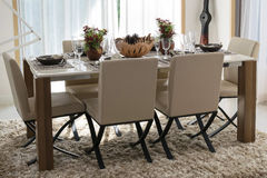 Dining table and comfortable chairs in modern home Stock Image