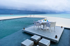 Dining table on the deck of swimming pool. Dining table on the deck of outdoor swimming pool in beach resort stock photos