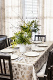 Decorated Christmas dining table. Dining table decorated for Christmas with eight place settings and evergreen centerpiece Stock Photography