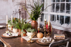 Dining table decorated for Christmas and evergreen centerpiece Royalty Free Stock Photography
