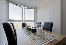 Dining table in a floor to ceiling window Stock Photos