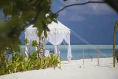Dining Table for Honeymoon couples at Tropical Beach. Dining table in the beach in Maldives. There is a branch out of focus in the midle of the frame, the table Royalty Free Stock Photography