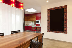 Dining table, kitchen in background Stock Photos