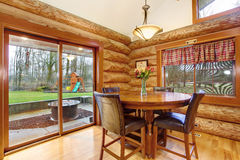 Dining table with leather chairs in log cabin house. Royalty Free Stock Images