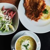 dining table:a plate of soup, risotto with cutlet and vegetable salad stock photo