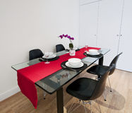 Dining table with red cloth. Modern luxury dining table with glass top and setup with red cloth Royalty Free Stock Images