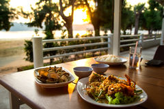 Dining table with seafoods with golden light on sunset. At seafoods restaurant nearby the beach Stock Image
