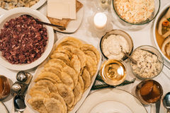 Dining table set with delicious food. High angle closeup of a dining table full of a variety of delicious traditional food and wine Royalty Free Stock Photo