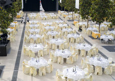 Dining table set for event. Large dining table set for wedding, dinner or another corporate event. The tables are with beautiful decoration standing in a large Royalty Free Stock Photo