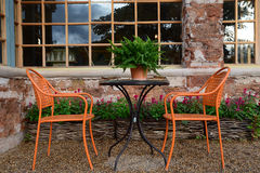 Dining table set in lush garden Royalty Free Stock Photos
