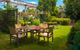 Dining Table set in Lush Landscaped Garden Royalty Free Stock Image