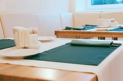 Dining table set up with cutlery in green napkins royalty free stock images
