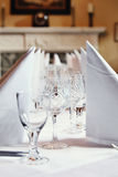 Dining Table Setting. A close up of a simple and elegant dining table setting with napkins and crystal wine glass. (Narrow Depth-of-field with sharp focus in the Stock Photography